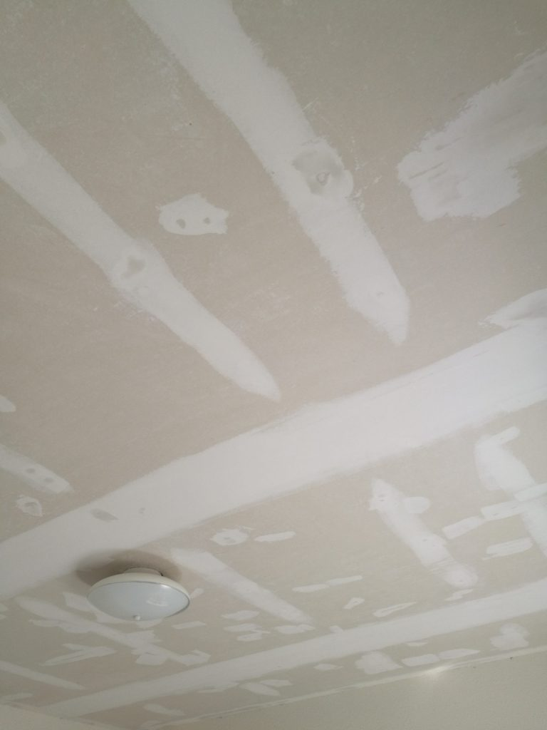 Scraped drywall ceiling covered in patches