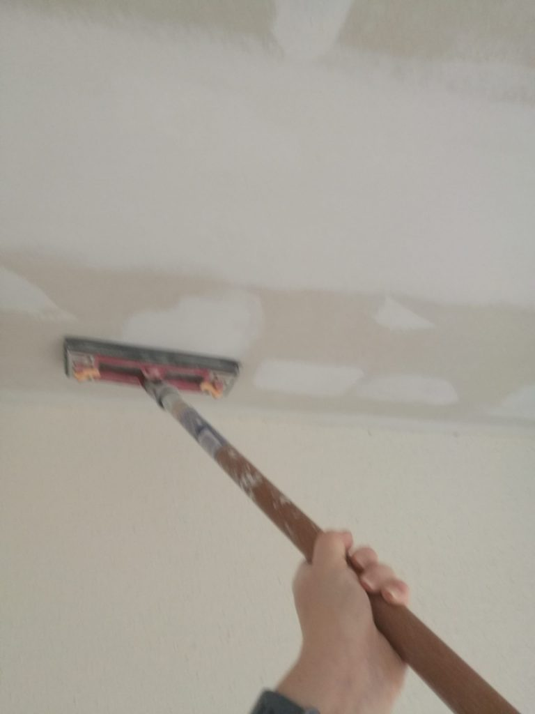 Sanding down the new joint compound on the ceiling